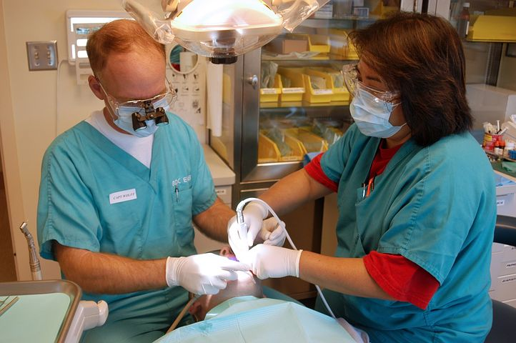 two dentists performing wisdom teeth removal to a patient in Mulgrave